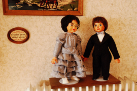 Hochzeitspaar als Puppen und Rosenblätter auf Boden